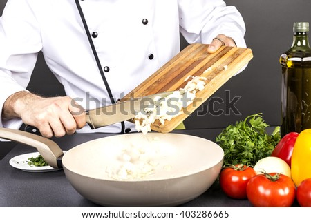 Chef putting chopped onion in the pan. Closeup - stock photo