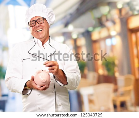 Chef Putting Coin In Piggy bank Isolated On Pink Background - stock photo