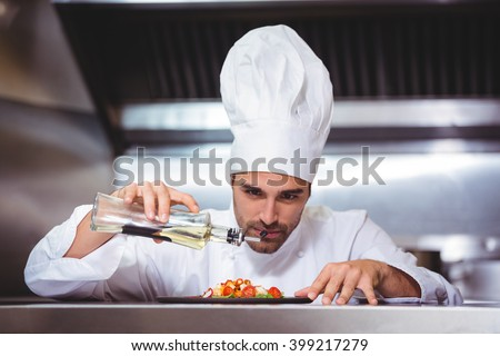 Chef putting finishing touch on salad in commercial kitchen - stock photo