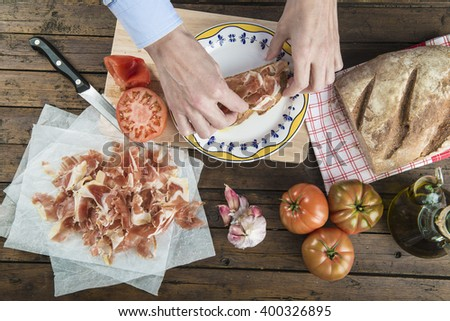 Chef putting ham  on a slice of bread with olive oil, garlic and tomato - stock photo