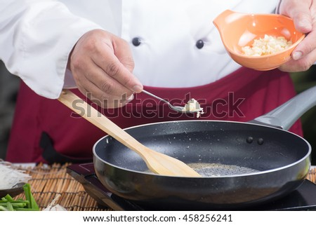 Chef putting minced garlic for cooking Pad Thai / cooking Pad Thai concept