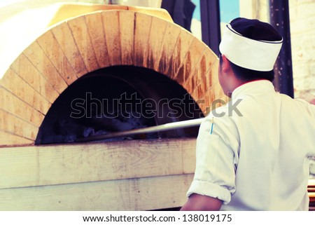 Chef putting pizza in wood fire oven - stock photo