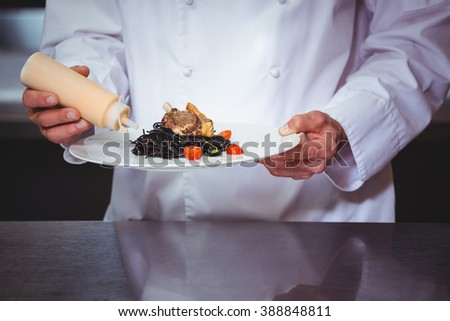 Chef putting sauce on a dish of spaghetti in commercial kitchen - stock photo