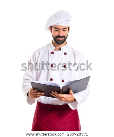 Chef reading a book - stock photo