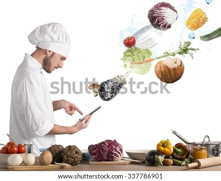Chef reads a recipe from the tablet - stock photo