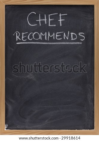 chef recommends title handwritten with white chalk on blackboard with eraser smudges, copy space below - stock photo
