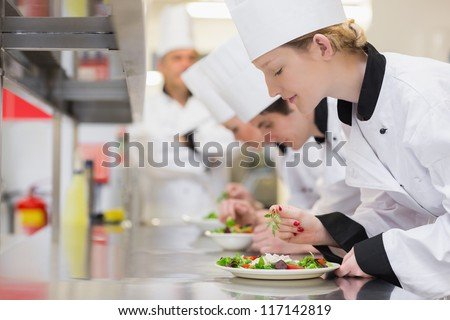Chef's finishing their salads in culinary class in kitchen
