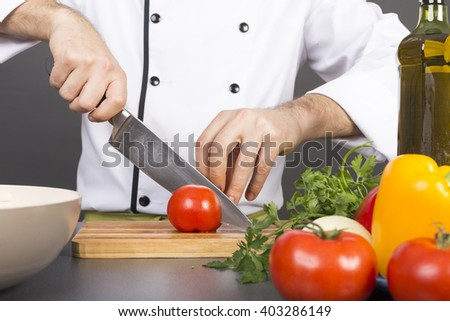 Chef's hands cutting a red fresh tomato on a wooden board
