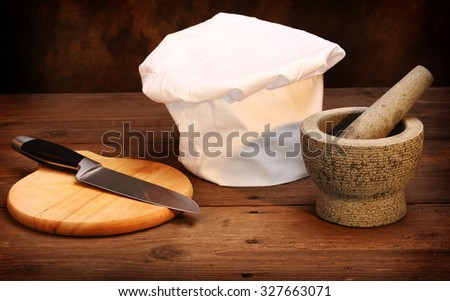chef's hat, mortar and cooking knife  - stock photo