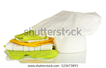Chef's hat with kitchen towels and potholders isolated on white - stock photo