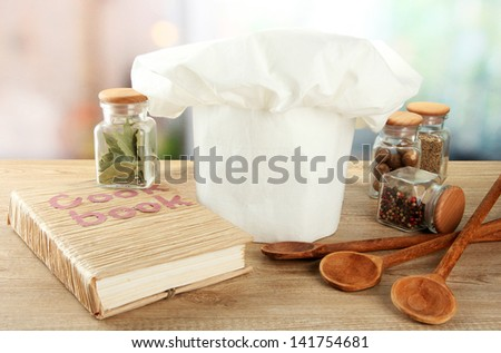 Chef's hat with spoons on table in kitchen - stock photo