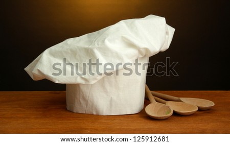 Chef's hat with spoons on table on brown background - stock photo