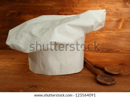 Chef's hat with spoons on wooden background - stock photo