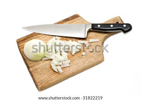 Chef's knife hopping an onion on an old wooden cutting board - white background. - stock photo
