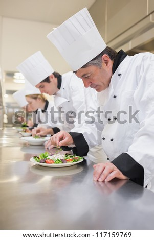 Chef's preparing their salads in the kitchen - stock photo