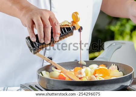 chef seasoning to pork and vegetable curry in frying pan - stock photo