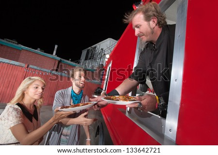 Chef serving carryout pizza from food truck