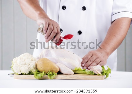Chef shaking a seasoning to raw chicken for meal time - stock photo