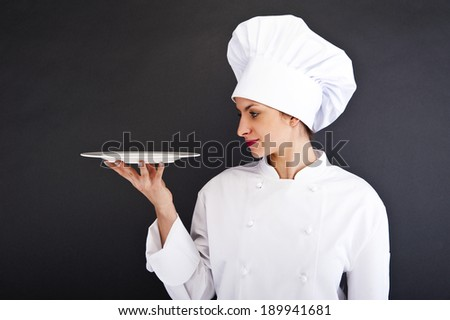 Chef showing empty plate. Happy smiling portrait of female in chef uniform and chef hat isolated on dark background.  - stock photo