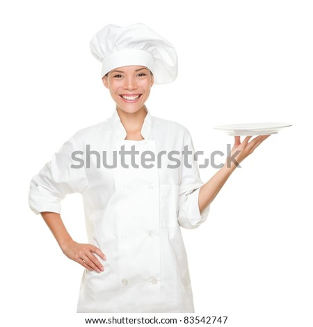 Chef showing empty plate. Happy smiling portrait of female in chef uniform and chef hat isolated on white background. Asian Caucasian woman model. - stock photo