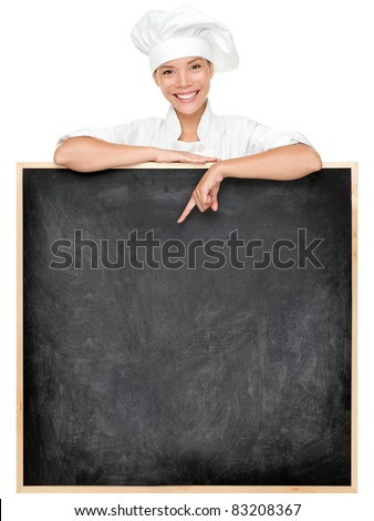 Chef showing menu sign blackboard smiling happy. Empty menu chalkboard with copy space for text. Female chef, baker or cook isolated on white background. Mixed race Asian Caucasian female model. - stock photo