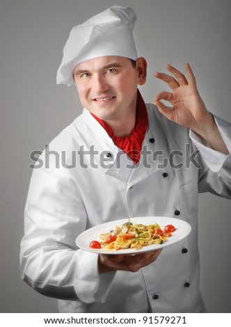 Chef showing plate with italian pasta - stock photo