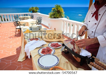 "Chef slicing ""Parma ham"" on wedding buffet on a beautiful terrace overlooking the sea - stock photo"