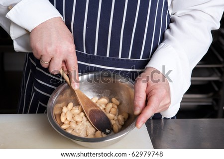 Chef squash beans with wooden spoon