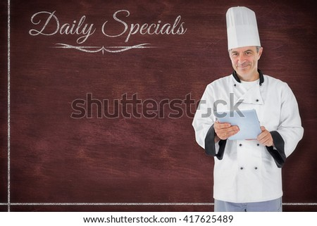 Chef standing holding a document against image of a desk