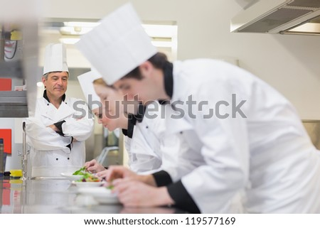 Chef supervising others making salads in kitchen
