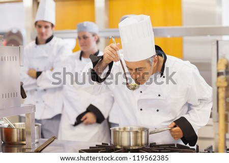 Chef tasting his students work in kitchen