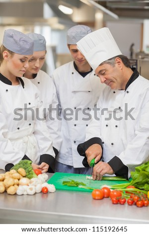 Chef teaching cutting vegetables to three trainees in the kitchen - stock photo