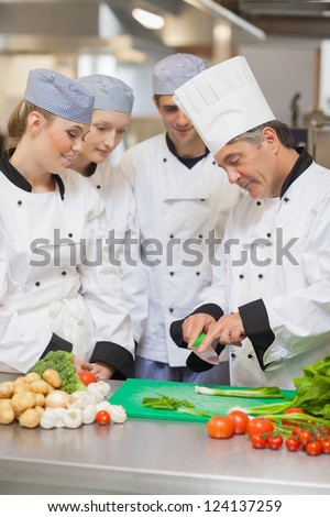 Chef teaching trainees how to cut vegetables in the kitchen - stock photo