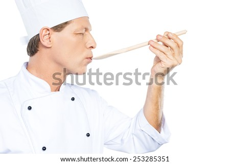 Chef trying meal. Side view of confident mature chef in white uniform keeping eyes closed while trying eating from wooden spoon and standing against white background - stock photo
