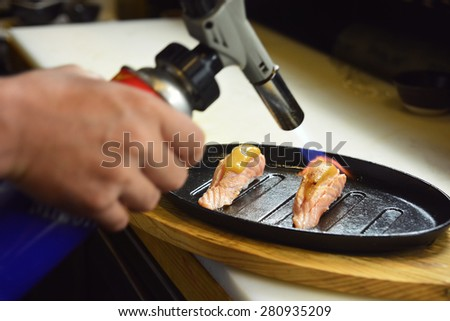 chef using a torch burn on Miso sauce - Salmon Saikyo sushi - stock photo
