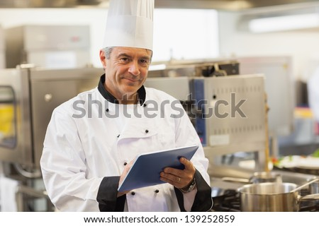 Chef using his digital tablet and looking at camera in the kitchen - stock photo