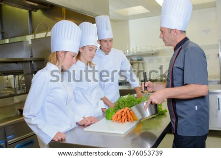 Chef whisking ingredients in front of students - stock photo
