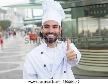 Chef with beard showing thumb in front of a restaurant - stock photo