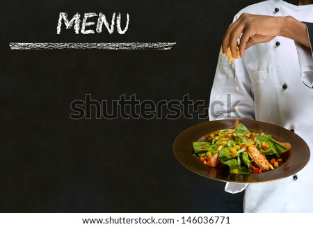 Chef with healthy salad food on chalk blackboard menu writing background - stock photo