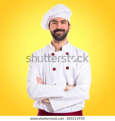 Chef with his arms crossed over colorful background - stock photo