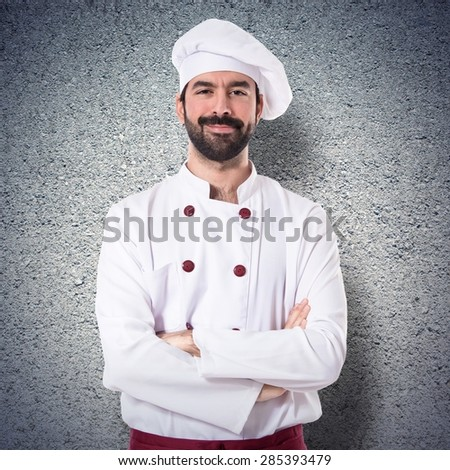 Chef with his arms crossed over textured background - stock photo