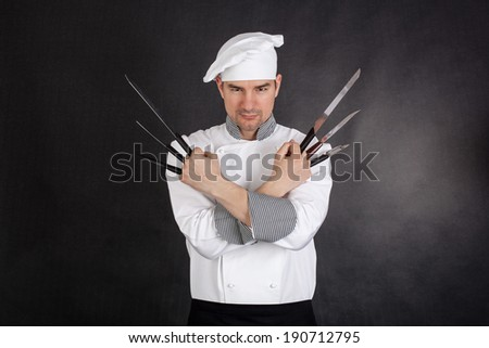 Chef with knifes arms crossed on black background - stock photo