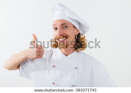 Chef with long red hair in white uniform look at the camera, show big finger up and smile. Cooking the meal. Horizontal portrait of chef - stock photo