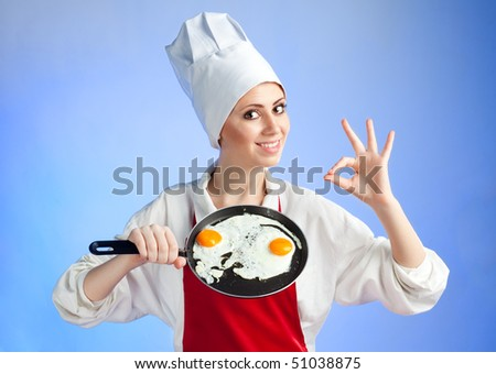 Chef with pan and frying egg ready to serve breakfast - stock photo