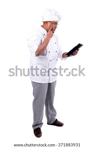 Chef with tablet checking a recipe - stock photo