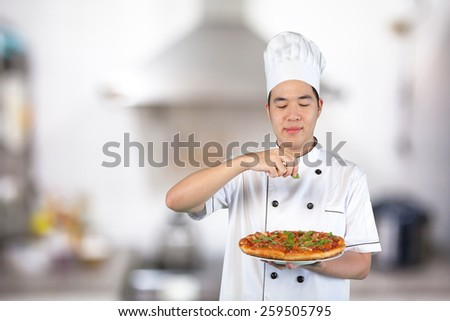 Chef with white uniform cooking pizza in the kitchen