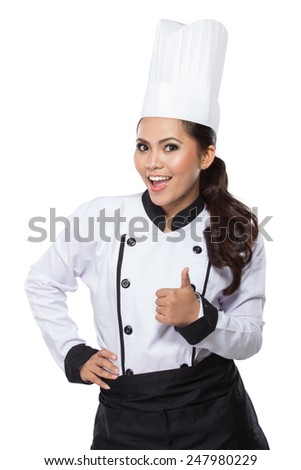 Chef woman - happy thumbs up. Smiling and cheerful female chef, cook or baker in uniform and hat over gray background - stock photo