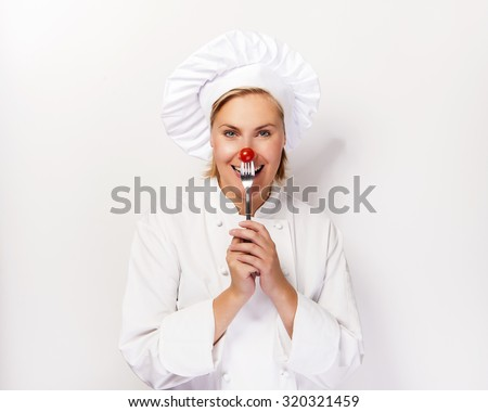 Chef woman holding a fork with tomato against her nose, standing against white background smiling. - stock photo