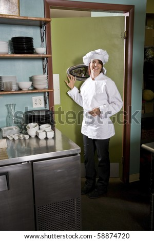 Chef working in restaurant standing at kitchen doorway