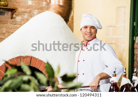 chef working in the kitchen near the fiery furnace, traditional cooking - stock photo